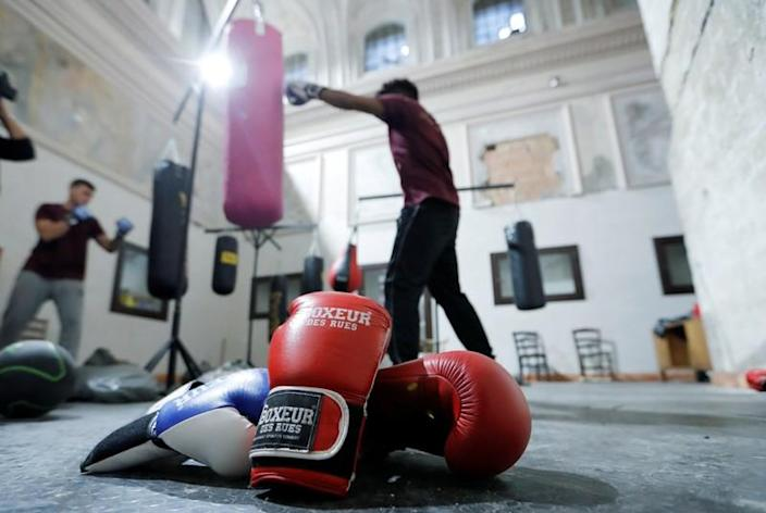 Boxing gloves lie on the floor as Nico Rodrigues, 21, trains during a boxing class at the Santa Maria della Sanita Basilica in the Rione Sanita neighbourhood in Naples