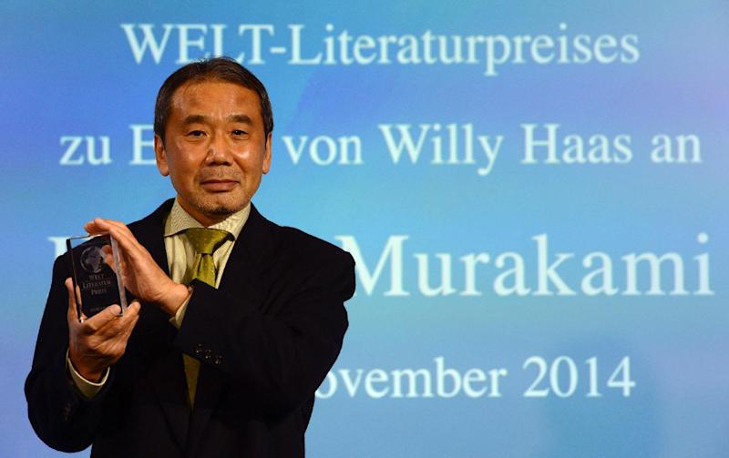 Japanese novelist Haruki Murakami poses with his trophy prior to an award ceremony for the Germany's Welt Literature Prize bestowed by the German daily Die Welt, in Berlin on November 7, 2014