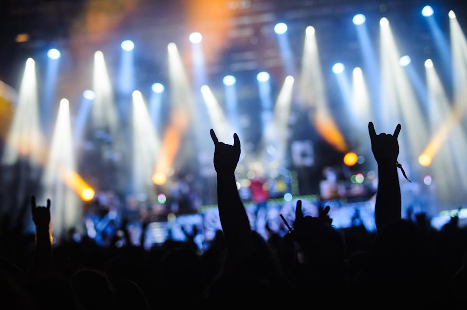 Hand raised showing a heavy metal rock sign, devil horns on a concert in crowd