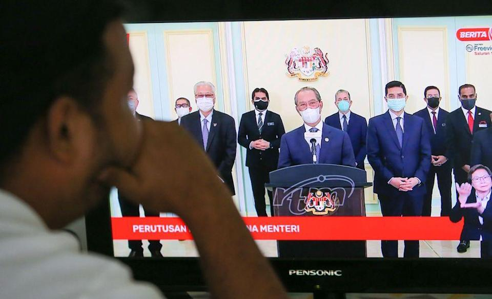 A man watches a live telecast of Prime Minister Tan Sri Muhyiddin Yassin's speech in Ipoh August 4, 2021. — Picture by Farhan Najib