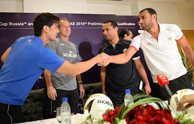 Philippine's team captain Philip Younghusban (L) shakes hands with Bahrain's Aied Mohamed Jaffar after a pre-match press conference in Manila on June 10, 2015 (AFP Photo/Ted Aljibe)