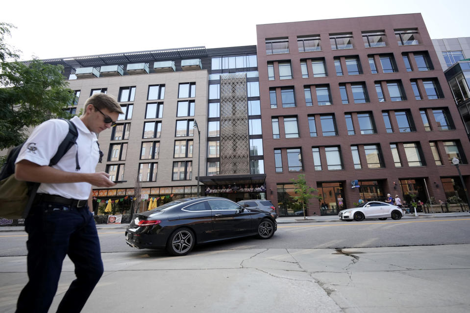 """A pedestrian moves past the Maven Hotel Sunday, July 11, 2021, in lower downtown Denver. Authorities said four people have been arrested on drug and weapons charges after a """"report of a suspicious occurrence"""" at the downtown Denver hotel, which is located near Coors Field, the site of Major League Baseball's 2021 All-Star Game. Denver police said officers responding to a tip searched two rooms at the hotel on Friday night. (AP Photo/David Zalubowski)"""
