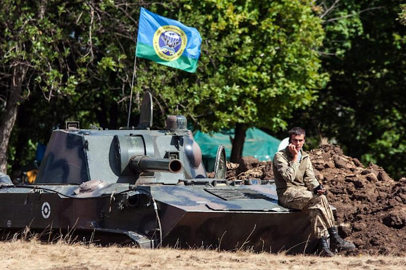 A Ukrainian serviceman sits on a tank while speaking on the phone inside a military camp in the Donetsk region, on August 29, 2014 (AFP Photo/Oleksandr Ratushniak)