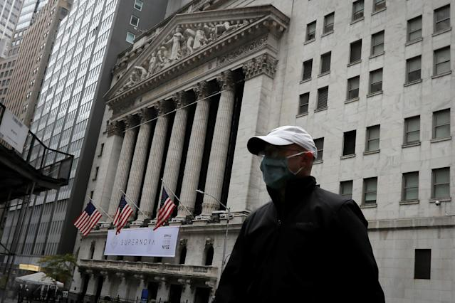 A man wearing a protective face mask walks past the New York Stock Exchange in Manhattan in New York City, New York, U.S., October 26, 2020. REUTERS/Mike Segar