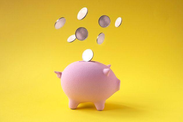 Coins falling into pink piggy bank on yellow background. (Photo: twomeows via Getty Images)