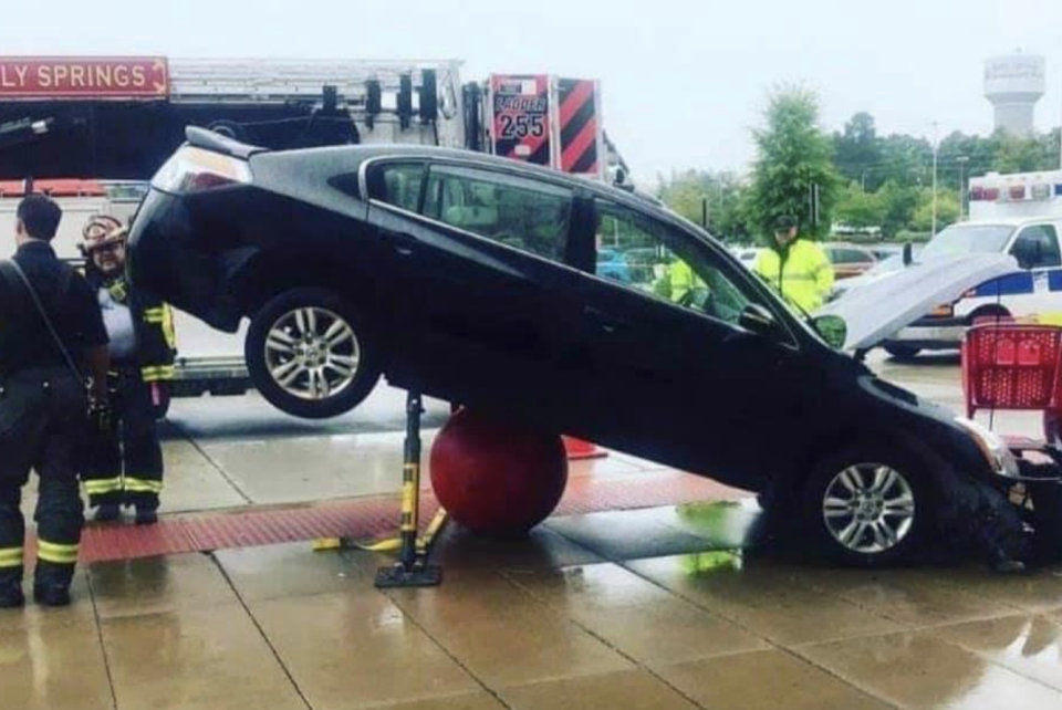 A car parked on top of a concrete bollard outside of Holly Springs Target.