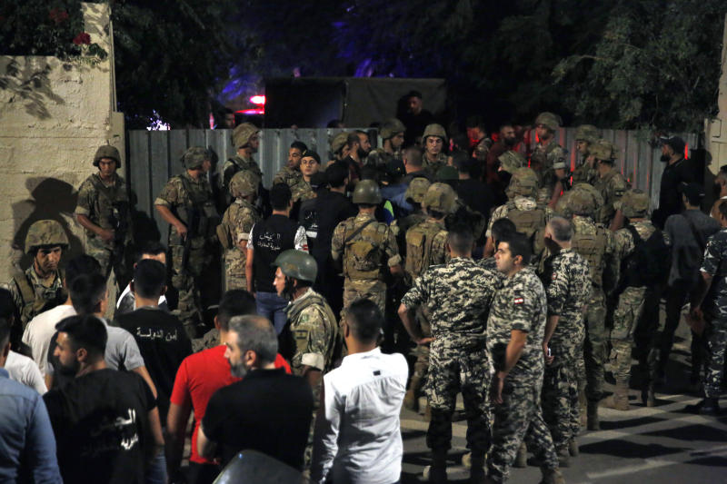 Lebanese security stand near the site where an Israeli drone was said to have crashed in a stronghold of the Lebanese Hezbollah group, in a southern suburb of Beirut, Lebanon, Sunday, Aug. 25, 2019. A Hezbollah official said Sunday that an Israeli drone went down over the Lebanese capital of Beirut and another exploded in the air, amid regional tensions between Israel and Iran. (AP Photo/Bilal Hussein)