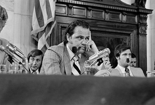 Sen. Fred Thompson, center, smokes a pipe as he listens to questions during the Senate Watergate Committee in Washington, July 11, 1973. Others are unidentified. (AP Photo)