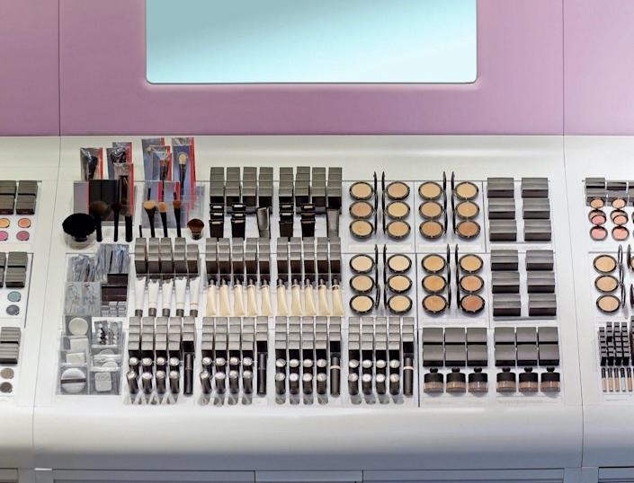 Makeup counter inside beauty store with shelf full of makeup products