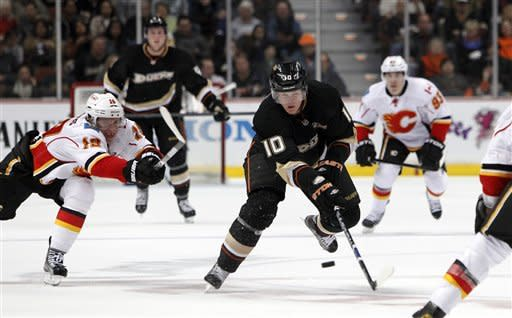 Anaheim Ducks right wing Corey Perry (10) controls the puck ahead of Calgary Flames right wing Tom Kostopoulos, left, in the second period of an NHL hockey game in Anaheim, Calif., on Monday, Feb. 6, 2012. (AP Photo/Christine Cotter)