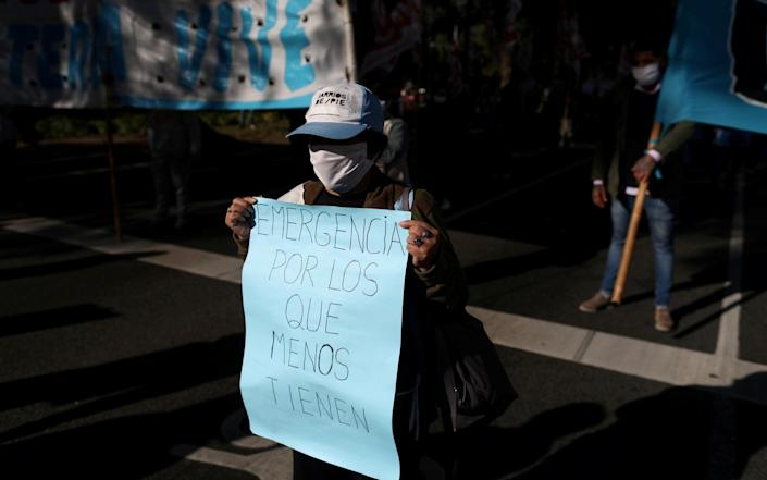 """A demonstrator wearing a face mask holds a placard that reads """"emergency for those who have least"""", during a protest to demand resources for the vulnerable in Argentina - Reuters"""