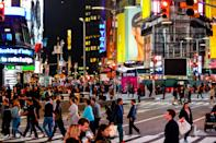 Times Square with tourists. Iconified as 'The Crossroads of the World' it's the brightly illuminated hub of the Broadway Theater District.