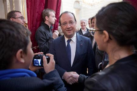 French President Francois Hollande greets visitors in the Elysee presidential palace in Paris