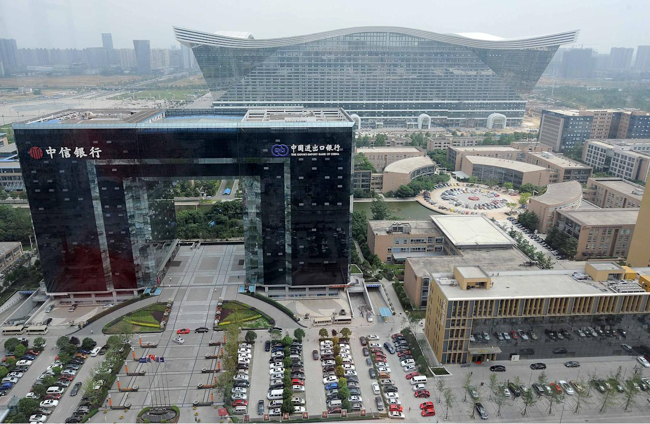 "The ""New Century Global Centre"" building (top) is seen standing among several buildings in Chengdu, in southwest China's Sichuan province on June 6, 2013. The center, claimed by Chinese officials as ""the world's largest standalone structure"", is going to be opened to the public on June 28. The 100m high ""New Century Global Centre"" is a symbol of the spread of China's boom: 500m long and 400m wide, with 1.7 million square metres of floor space - big enough to hold 20 Sydney Opera Houses, according to local authorities.  CHINA OUT     AFP PHOTO"