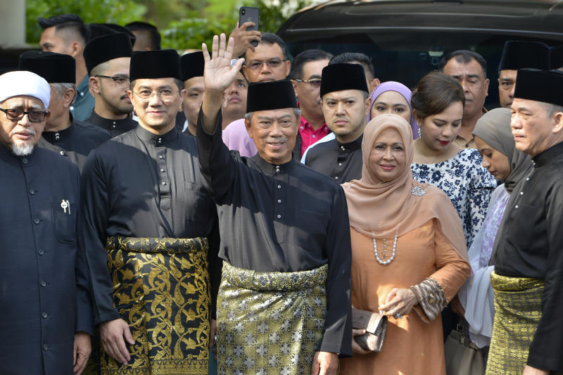 FILE PHOTO: In this March 1, 2020, file photo, Muhyiddin Yassin, center, waves with his family and supporters as he prepares to leave his house for the palace to swear in as new prime minister, in Kuala Lumpur, Malaysia. (AP Photo/Johnshen Lee, File)
