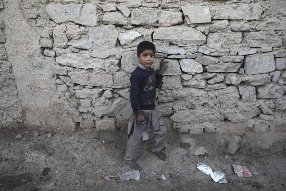 An internally displaced boy pose for a photograph outside his temporary home in the city of Kabul, Afghanistan, Wednesday, Dec. 30, 2020. Save the Children has warned that more than 300,000 Afghan children face freezing winter conditions that could lead to illness, in the worst cases death, without proper winter clothing and heating. (AP Photo/Rahmat Gul)