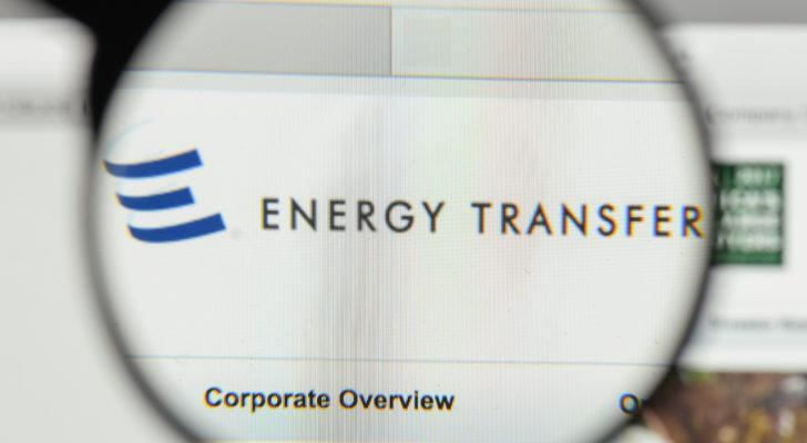 A magnifying glass zooms in on the website for Energy Transfer (ET).