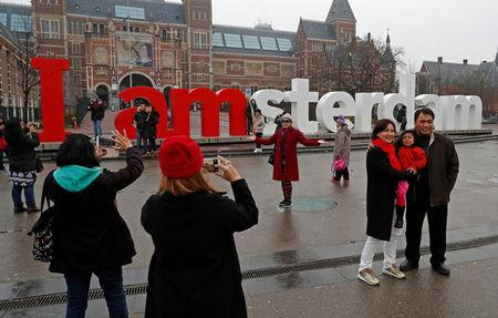 FILE PHOTO: Tourists pose for photos outside the Rijksmuseum in central Amsterdam, Netherlands, December 1, 2017.  REUTERS/Yves Herman/File Photo