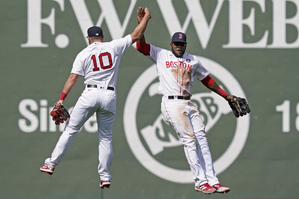Boston Red Sox outfielders Hunter Renfroe (10) and Franchy Cordero, right, celebrate their 11-4 victory over the Chicago White Sox after a baseball game at Fenway Park, Monday, April 19, 2021, in Boston. (AP Photo/Elise Amendola)