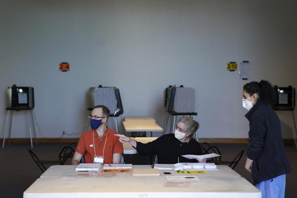Election judges Andrew Olson, left, and Sandra Hunter, show voter Riya Madan where to cast her ballot inside the Frederick R. Weisman Art Museum at the University of Minnesota in Minneapolis on Tuesday, Aug. 11 2020. (Anthony Souffle/Star Tribune via AP)