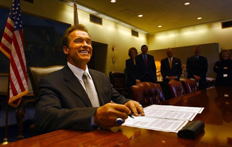 Gov. Arnold Schwarzenegger signs an executive order lowering the car tax shortly after being sworn into office in 2003.