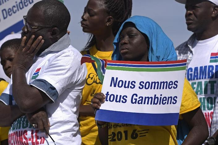 """A demonstrator holds a sign reading """"We are all Gambians"""" as Senegalese NGOs and civil rights groups held a protest rally in Dakar on December 17 (AFP Photo/SEYLLOU)"""