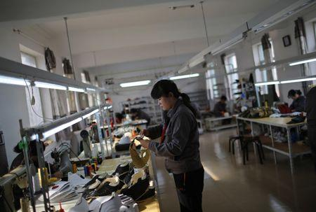 File photo: North Korean workers make soccer shoes inside a temporary factory at a rural village on the edge of Dandong