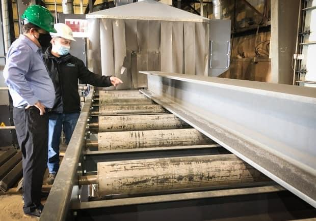 Jamie MacNeil of BigMoon Power and Joe Hines of East Coast Metal Fabrication look over a steel beam that will be used to build BigMoon's first commercial tidal power unit. (Tom Ayers/CBC - image credit)