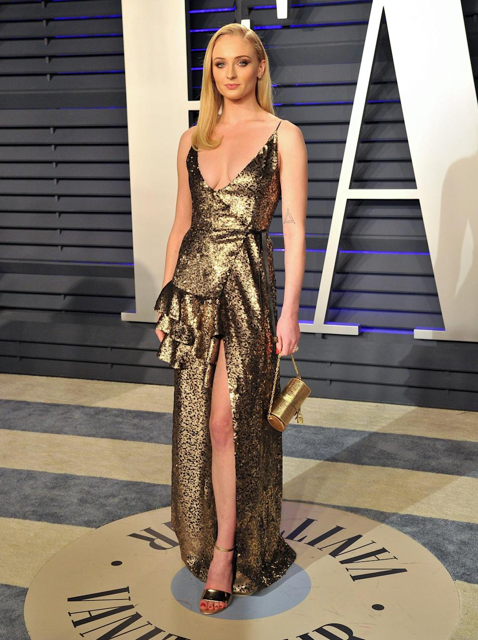 <p>Sophie accessorized this gold-sequined, ruffle-tier Louis Vuitton wrap dress with a cylinder miniaudière from the brand and metallic heels at the Vanity Fair Oscars party in 2019.</p>