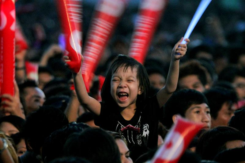 A young girl cheers while watching American singer-songwriter Jason Mraz perform at the base of the famous hilltop Shwedagon Pagoda in Yangon, Myanmar, on Sunday, Dec. 16, 2012. Mraz mixed entertainment with education to become the first world-class entertainer in decades to perform in Myanmar, with a concert to raise awareness of human trafficking. (AP Photo/Zin Chit Aung)