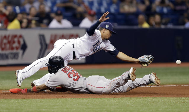 Tampa Bay Rays shortstop Willy Adames dives for a wild throw from first baseman Brad Miller as Boston Red Sox's Eduardo Nunez slides into third base during the seventh inning of a baseball game Thursday, May 24, 2018, in St. Petersburg, Fla. Nunez went in to score on the play. (AP Photo/Chris O'Meara)