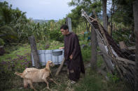 Seminarian Alfredo Santos, 21, brings water to a goat at the drug rehabilitation center in Mission San Francisco de Asis, Honduras, Tuesday, June 29, 2021. A year ago, Brother Santos, who used to go out to pray on the road, was kidnapped, beaten, doused with gasoline and subjected to a simulated hanging. He still is not able to talk about it. (AP Photo/Rodrigo Abd)