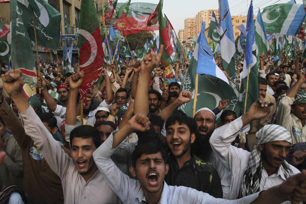 Supporters of the Pakistani religious party Jammat-e-Islami and Tehreek-e-Insaf party, headed by cricketer-turned politician Imran Khan, hold up their parties' flags and chant slogans during a rally against U.S. drone strikes in Pakistani areas, in Karachi, Pakistan, Sunday, Nov. 24, 2013. (AP Photo/Fareed Khan)