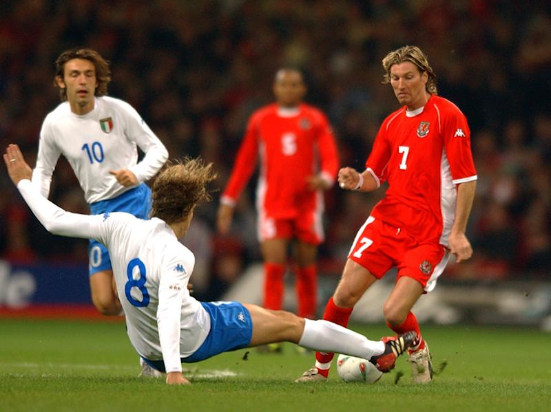 CARDIFF - OCTOBER 16: Massimo Ambrosini (No.8) of Italy tackles Robbie Savage of Wales during the 2004 European Champioship Group 9 Qualifying match between Wales and Italy on October 16, 2002 played at the Millennium Stadium in Cardiff, Wales. Wales won the match 2-1. (Photo by Shaun Botterill/Getty Images).