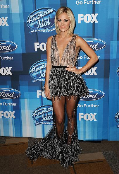 <p>Prior to performing a duet with Keith Urban, Carrie Underwood posed for pictures in an elegant form of a naked dress. Her Yanina couture number was all covered up but featured a sheer panel skirt that completely showed off her legs. <i>(Photo: Getty Images)</i></p>