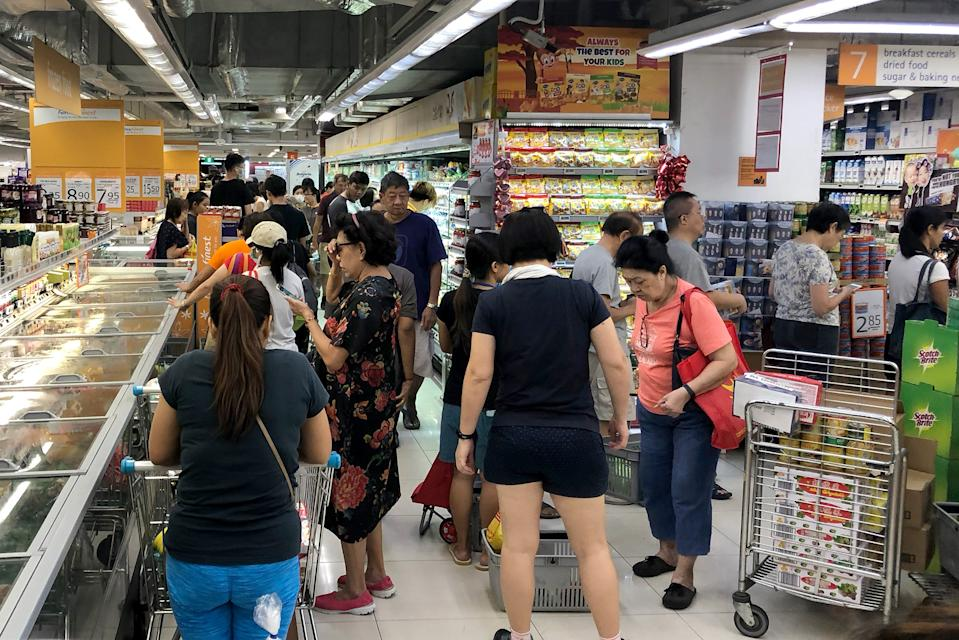 Long lines of shoppers seen inside a FairPrice Finest outlet in Clementi Mall on 17 March 2020. (PHOTO: Yahoo News Singapore file photo)