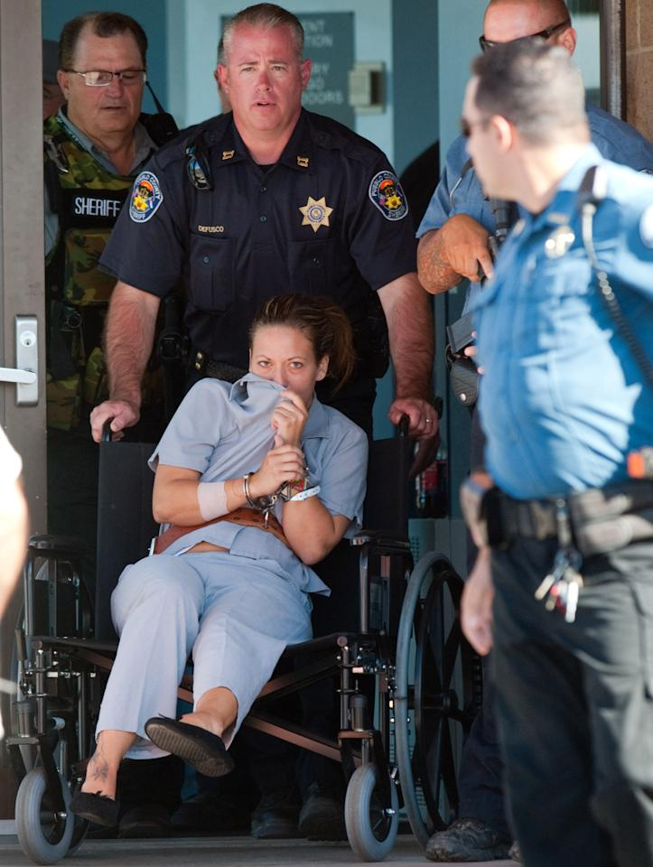 Lee Grace Dougherty, 29, in wheelchair, is wheeled by Pueblo County Sherrif's Office Capt. Liede DeFusco from Spanish Peak's Medical Center in Walsenburg, Colo., to a police vehicle on Wednesday, Aug. 10, 2011. She and her two brothers, accused of shooting at police in Florida and robbing a bank in Georgia, were captured Wednesday in Colorado after crashing their car into a highway barrier during a high-speed chase. (AP Photo/The Pueblo Chieftain, Mike Sweeney)