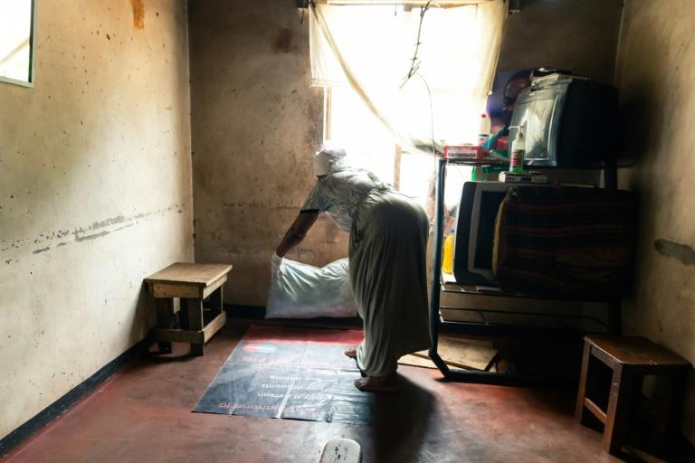 Where a child is born: Esther Gwena, 69, who acts as a midwife but has no training, lays down sheets in her rundown apartment -- a makeshift maternity unit (AFP Photo/Jekesai NJIKIZANA)