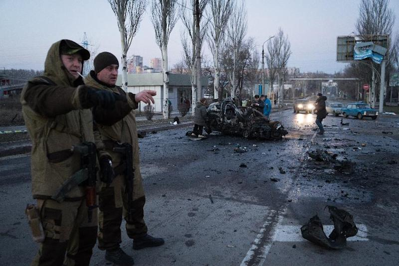 People inspect a destoyed car as pro-Russian rebels point in another direction following shelling that struck the Tekstylnyk district in the eastern Ukraine rebel stronghold of Donetsk, on Febuary 4, 2015 (AFP Photo/Andrey Borodulin)
