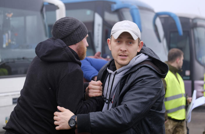 Pro-Russian prisoners greet each other during a prisoner exchange between Ukrainian and pro-Russian rebels sides, near the Maiorske checkpoint, Donetsk area, Ukraine, Sunday, Dec. 29, 2019. Ukrainian forces and Russia-backed rebels in the east have begun exchanging prisoners in a move aimed at ending their five-year-long war. (Yevgen Honcharenko/Pool Photo via AP)