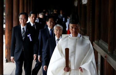 A group of lawmakers including Japan's ruling LDP lawmaker Otsuji are led by a Shinto priest as they visit Yasukuni Shrine in Tokyo