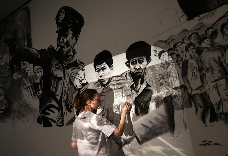 A local artist uses a projector to sketch a drawing in Tiravanija's installation (AFP Photo/ANDREW CABALLERO-REYNOLDS)