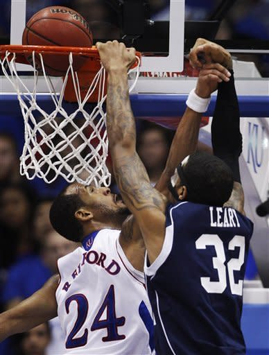 Kansas guard Travis Releford (24) alters a shot by Howard center Alphonso Leary (32) during the first half of an NCAA college basketball game in Lawrence, Kan., Thursday, Dec. 29, 2011. (AP Photo/Orlin Wagner)