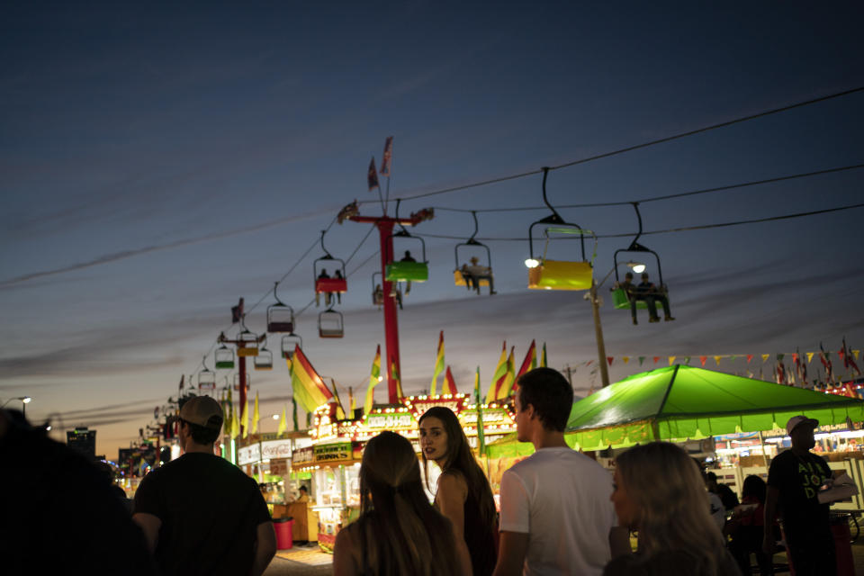 People walk between illuminated booths at the Mississippi State Fair on Wednesday, Oct. 7, 2020, in Jackson, Miss. At the fair, which is held every year in October and attracts people from across the racial spectrum, the vast majority of Black people are wearing masks. Most white people do not. (AP Photo/Wong Maye-E)