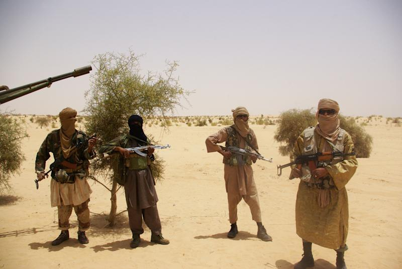 FILE - In this April 24, 2012 file photo, fighters from Islamist group Ansar Dine stand guard during a hostage handover in the desert outside Timbuktu, Mali. The Mali army attacked Islamist rebels with heavy weapons in the center of the country which divides the insurgent-held north and the government-controlled south, government officials said Thursday, Jan. 10, 2013. (AP Photo/File)