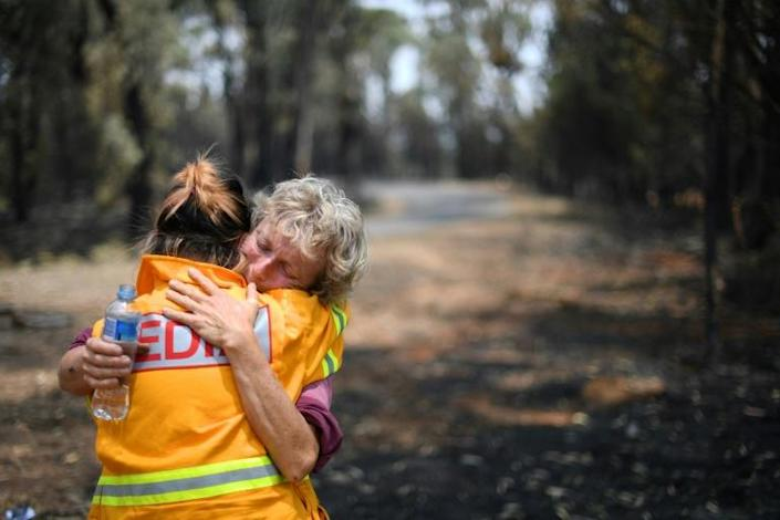 Orchard owner Stephenie Bailey hugs an AFP reporter after being overcome with emotion on her farm in Batlow, New South Wales (AFP Photo/SAEED KHAN)
