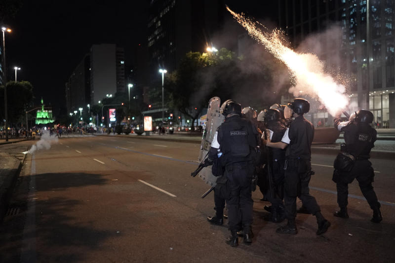 Police fire tear gas at a protest against government-proposed pension reforms during a strike in Rio de Janeiro, Brazil, Friday, June 14, 2019. The nationwide strike is the first since the arrival of far-right President Jair Bolsonaro on Jan. 1. (AP Photo/Leo Correa)