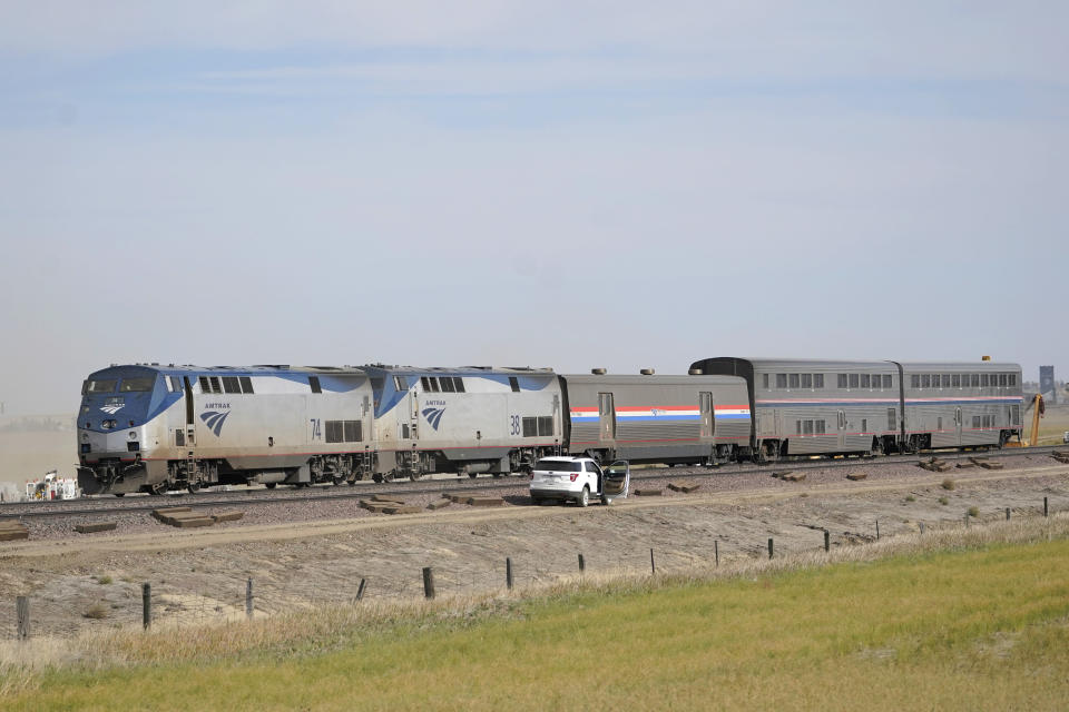 Engines and cars from an Amtrak train that derailed a day earlier are shown Sunday, Sept. 26, 2021, at the derailment site just west of Joplin, Mont.. The crash killed three people and injured others. The westbound Empire Builder was en route to Seattle from Chicago, with two locomotives and 10 cars. (AP Photo/Ted S. Warren)