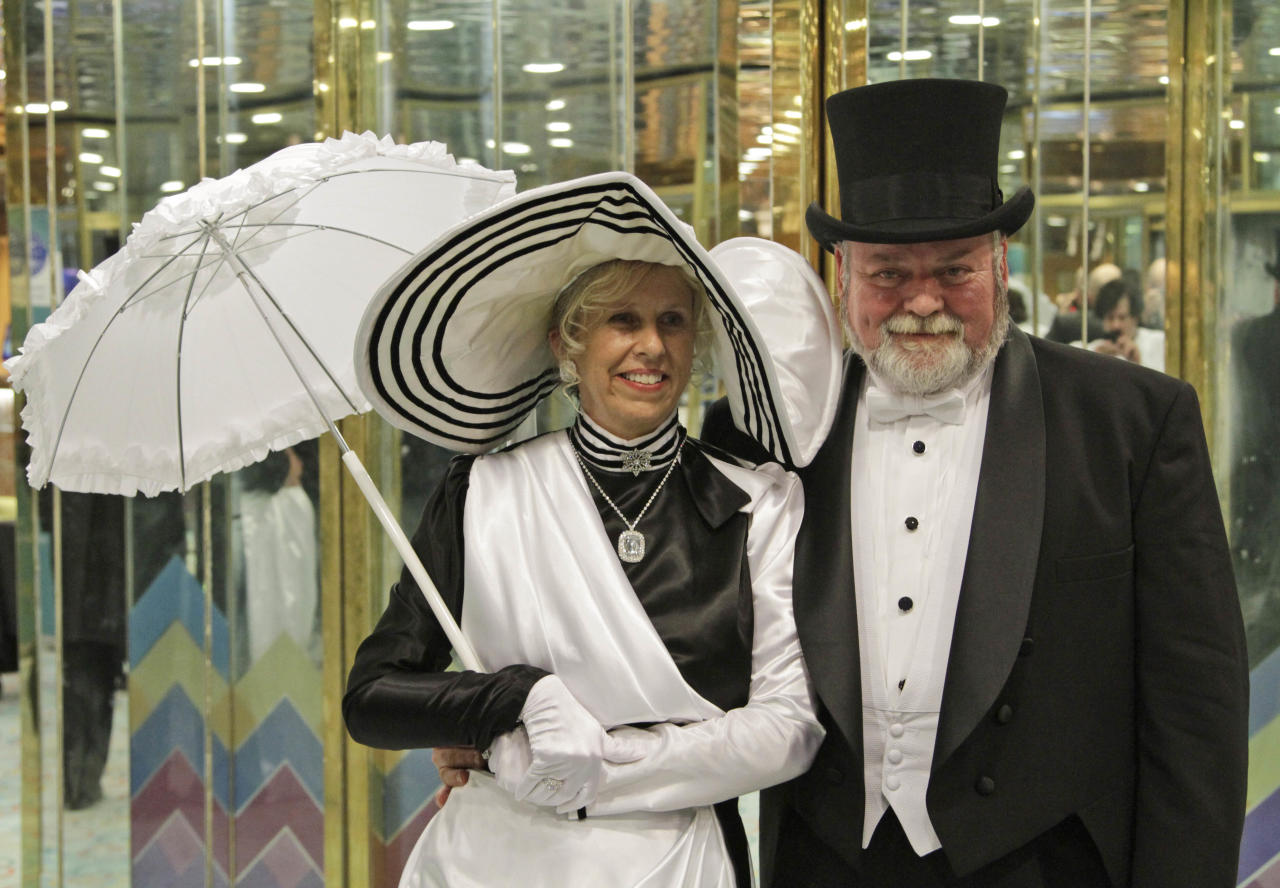 Americans Mike and Sherri Adgie from Atlanta, passengers of the MS Balmoral Titanic memorial cruise ship pose for pictures following a reception in the Atlantic Ocean, Friday, April 13, 2012. Nearly 100 years after the Titanic went down, the cruise with the same number of passengers aboard is setting sail to retrace the ship's voyage, including a visit to the location where it sank. The Titanic Memorial Cruise departed Sunday, April 8, from Southampton, England, where the Titanic left on its maiden voyage and the 12-night cruise will commemorate the 100th anniversary of the sinking of the White Star liner early Sunday, April 15, 2012. (AP Photo/Lefteris Pitarakis)