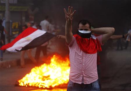 """A supporter of Mursi makes the """"Rabaa"""" or """"Four"""" gesture during clashes at Mohandiseen in Cairo"""
